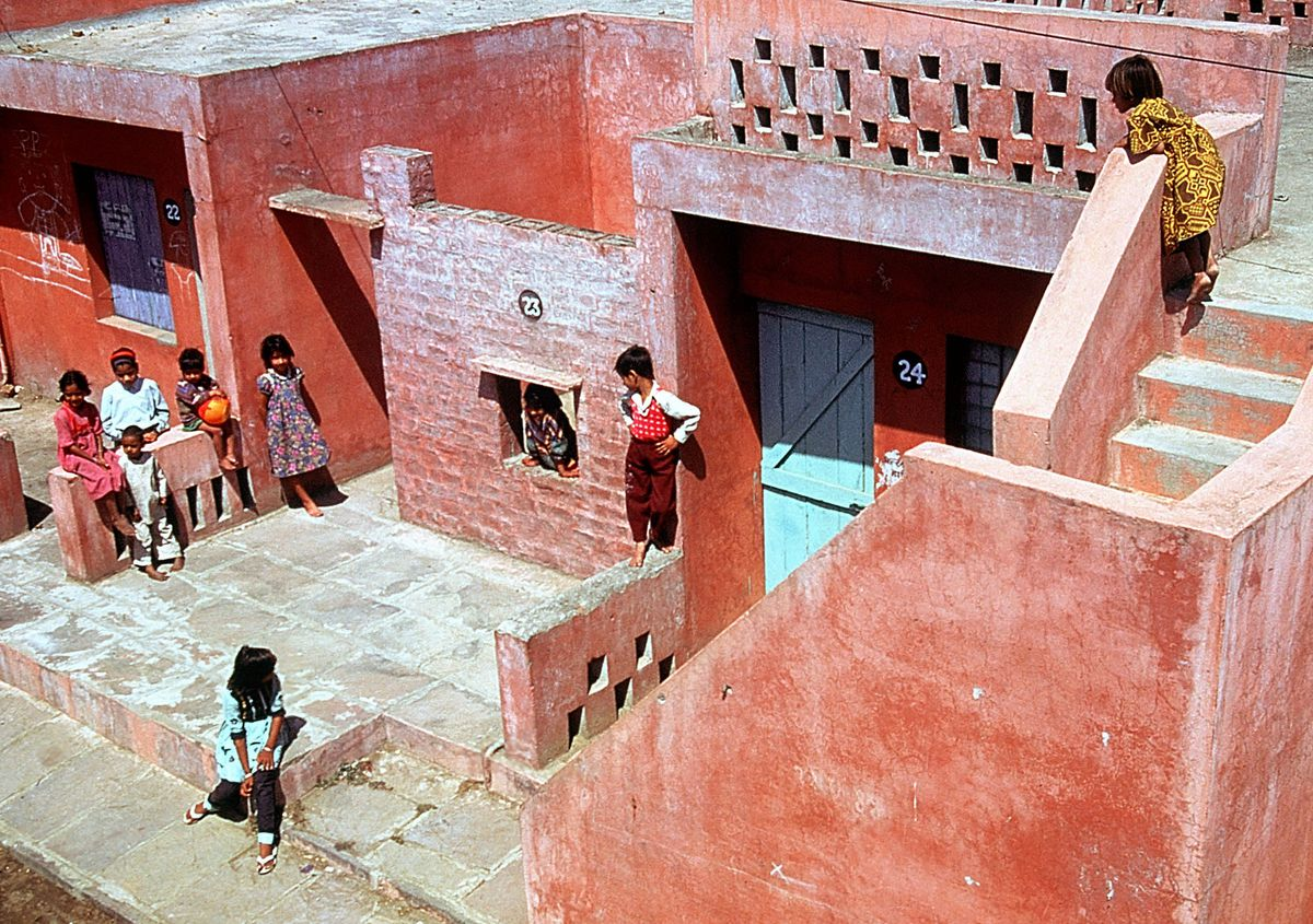 A community of pink modern multifamily homes where children are playing in the courtyard and walking down stairs.