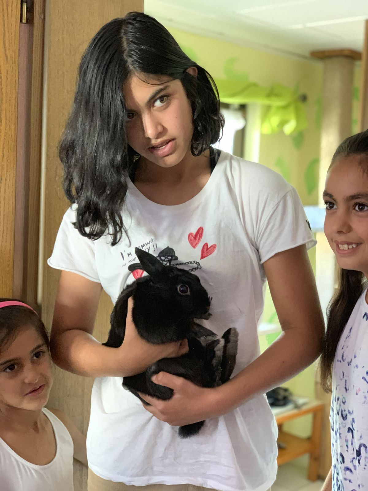 Fourteen-year-old Syrian refugee Hind Al Hammoud in her family's house in Neu-Anspach, Germany, holds a rabbit with her siblings looking on, Saturday, Sept. 14, 2019. Al Hammoud traveled with her family from their war-torn city to a small village in the Taunus mountain range of Germany where they are all working to integrate and heal from the trauma of the war and their flight.
