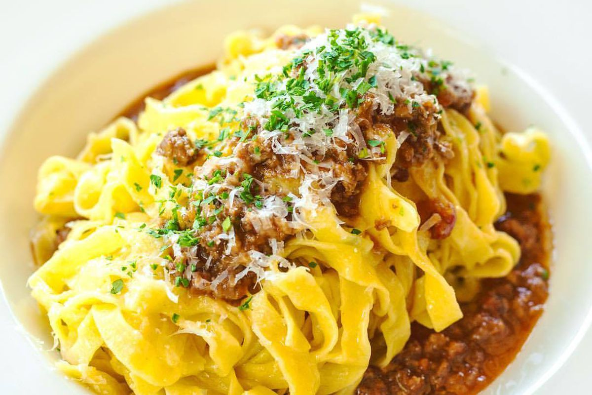 A white bowl of yellow noodles in a meat sauce topped with ground meat, shaved cheese, and herbs