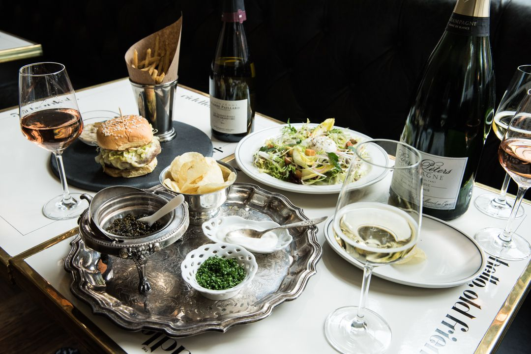 Bottles of Champagne and glasses of wine sit on a table with caviar, frisee salad, and a burger and fries