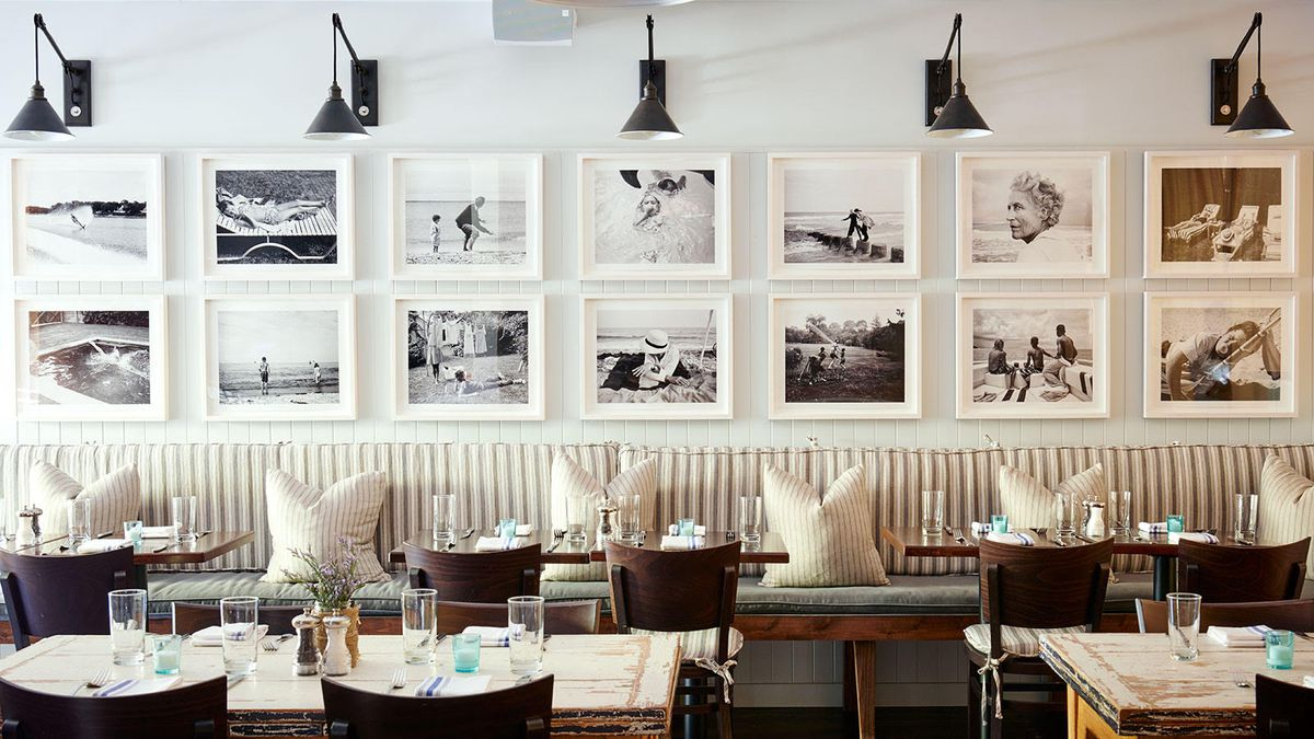 A white dining room with a wall of white framed photos over a banquette with pillows.