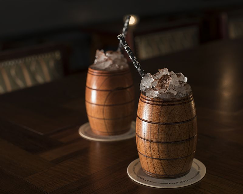 Two wooden glasses that look like wine barrels with ice sticking out.