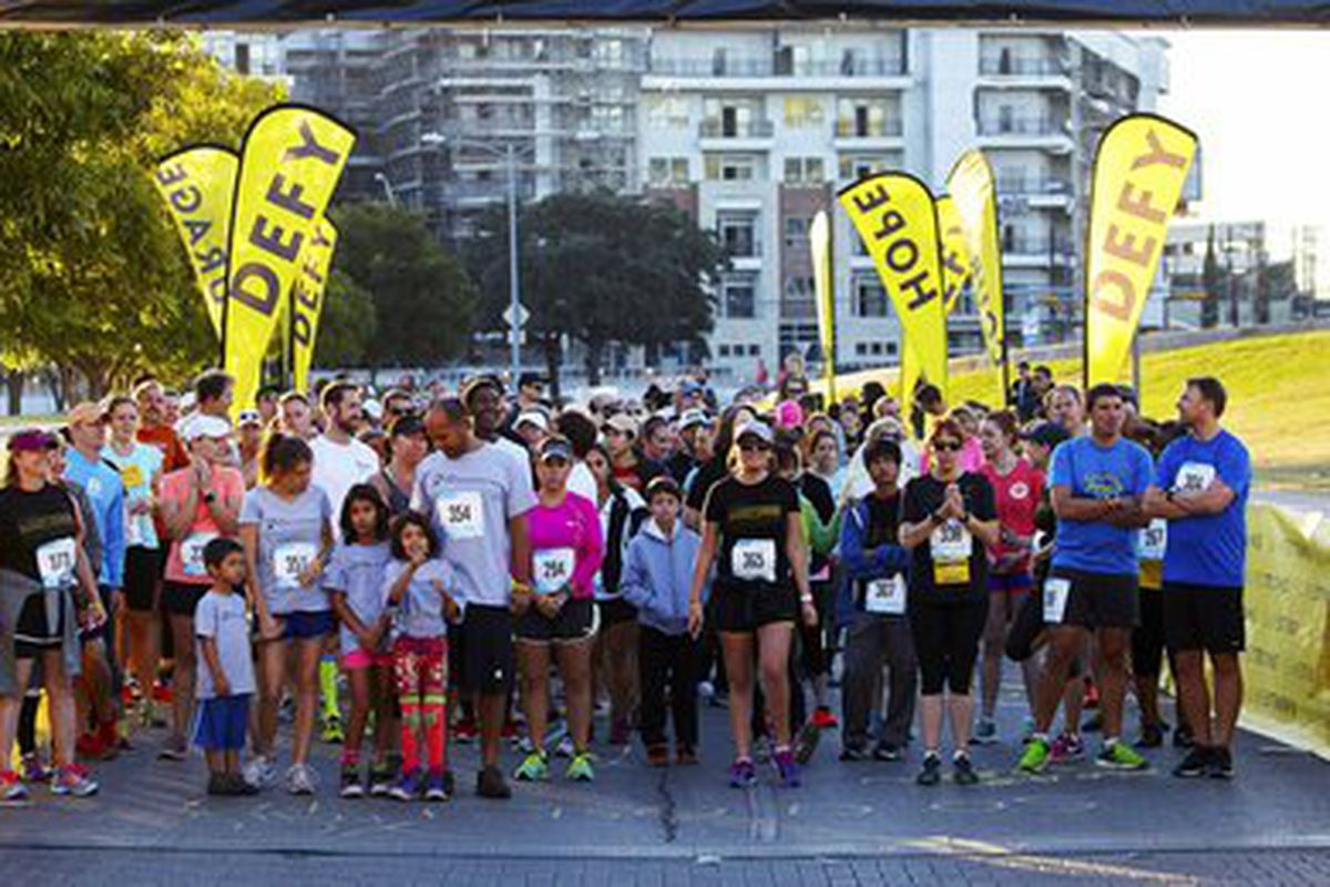 Photo of runners and walkers with yellow banners