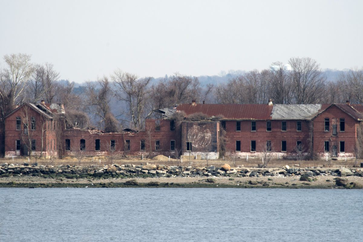 A photo of Hart Island, water surrounding it, and an abandoned building with trees behind.