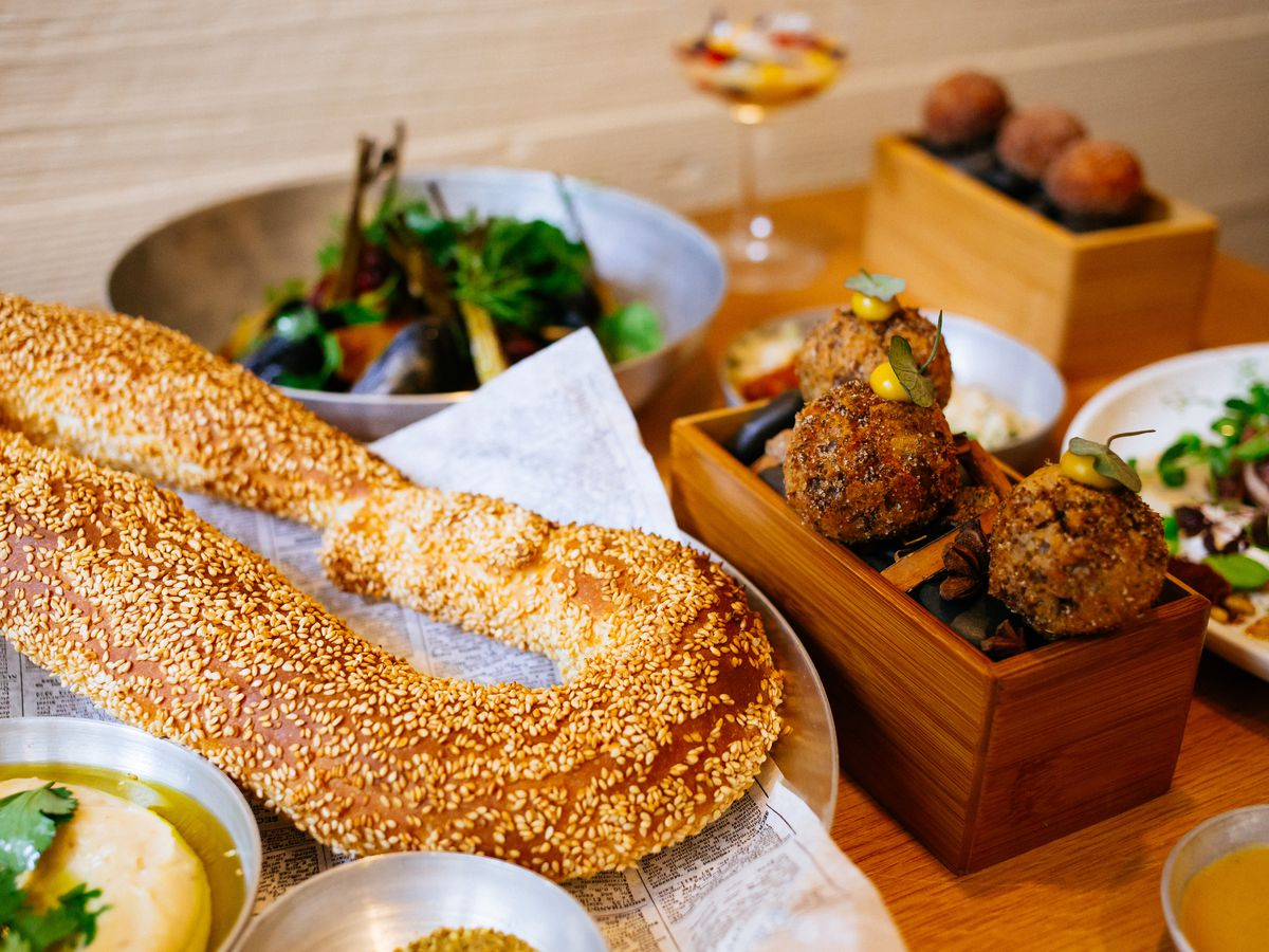 A spread of food from Nur, including a sesame-studded bread product and round balls on wooden boxes.