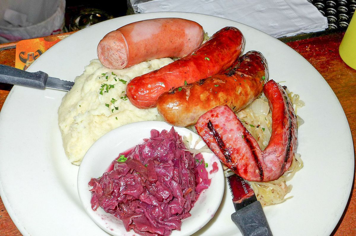 A white plate with mashed potatoes, several sausages, and a smaller plate with red cabbage.