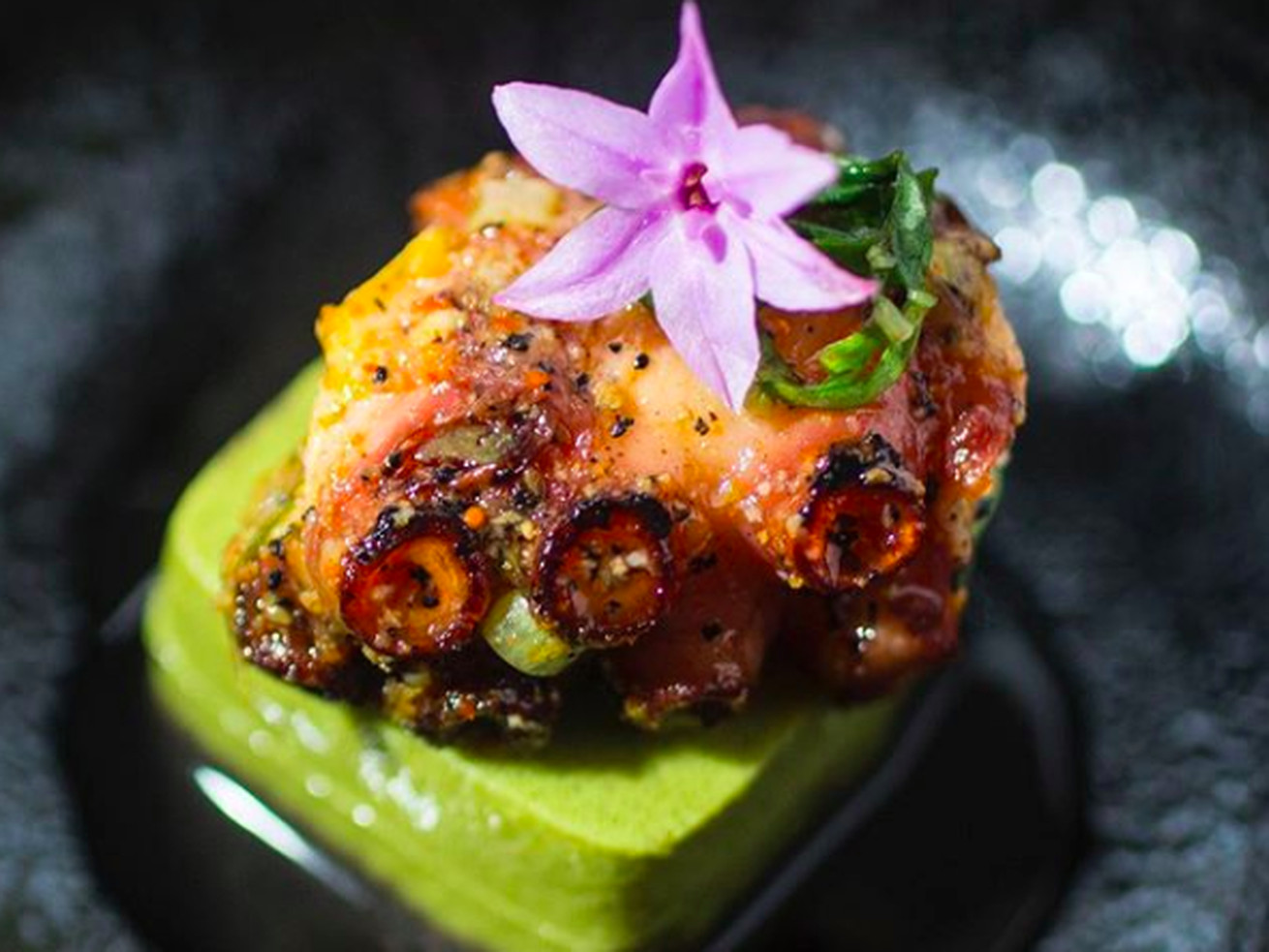 A place of octopus with a flower on a dark plate.