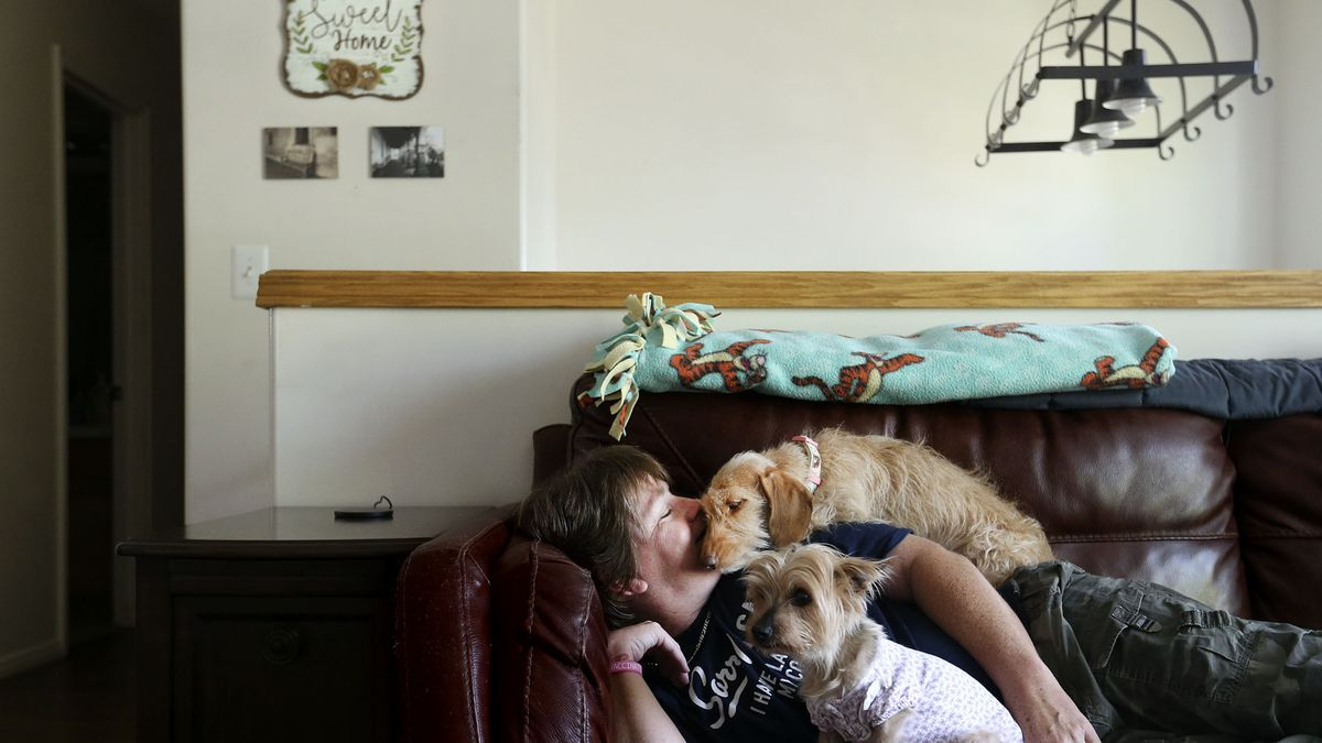 Sherry Munsell relaxes with her dogs after work in her Clinton home on Tuesday, June 15, 2021. Munsell earns $17 an hour as a truck driver and occasionally struggles to pay rent.