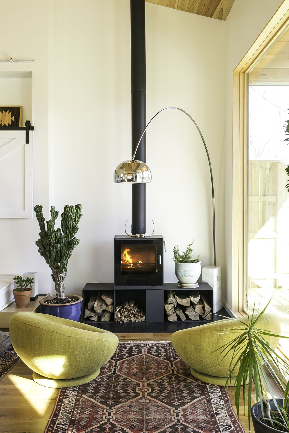 Black fireplace, chartreuse chairs facing the fireplace, many plants and rug.