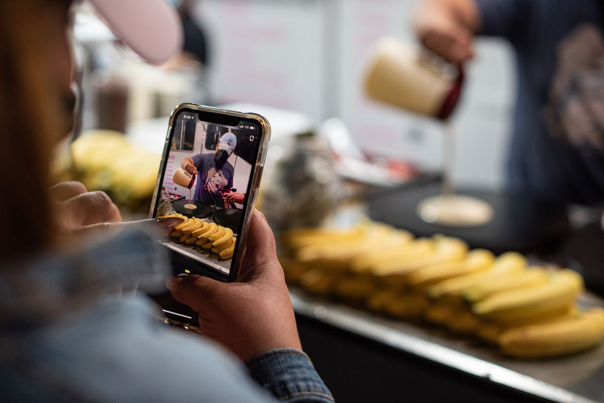 A hand holding a phone to take a video of a person making a crepe.