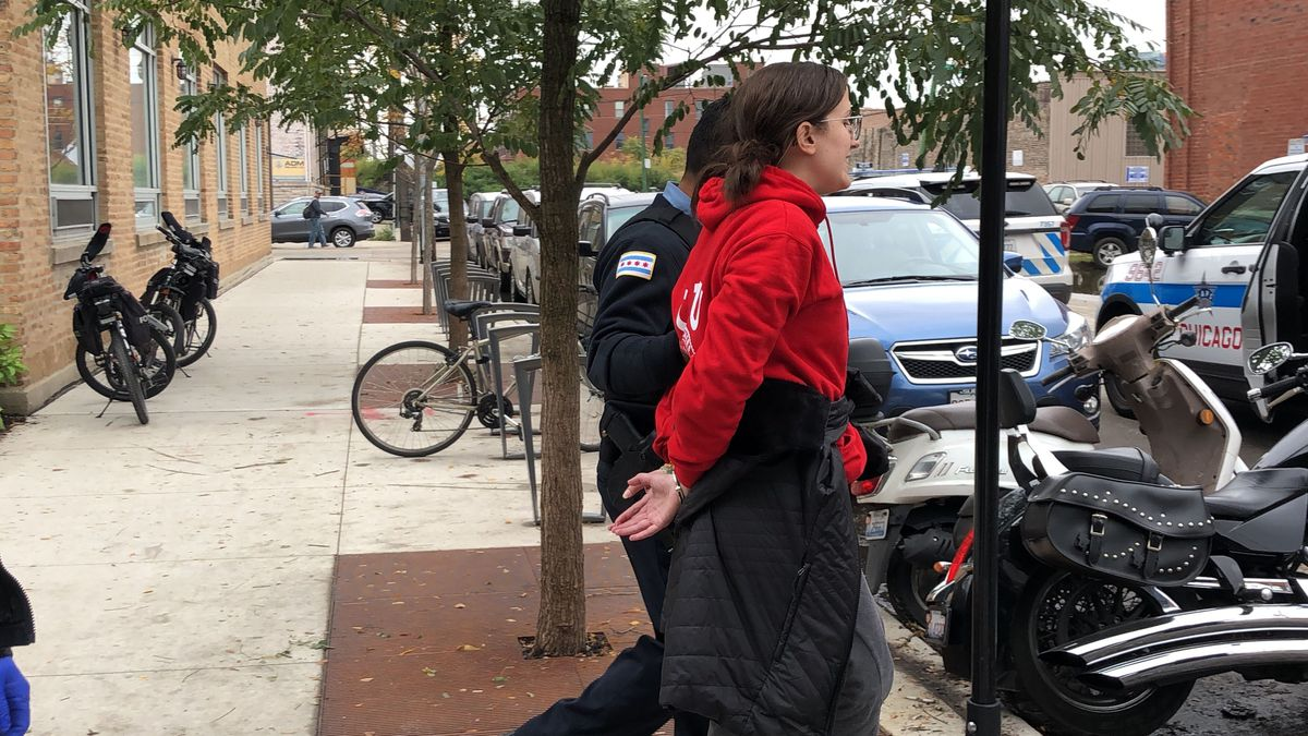 A protester wearing a Chicago Teachers Union shirt was led away by police during an afternoon protest on the teachers strike's ninth day.