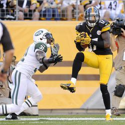 Pittsburgh Steelers wide receiver Mike Wallace (17) makes a catch for a touchdown in front of New York Jets cornerback Antonio Cromartie (31) in the third quarter of an NFL football game on Sunday, Sept. 16, 2012, in Pittsburgh. The touchdown call was confirmed after replay.