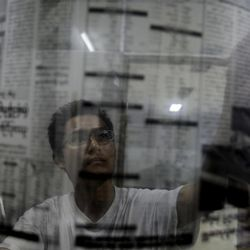 """Graphic designer of Myanmar's weekly newspaper """"Weekly Eleven"""" looks at the film of the next morning's edition of the newspaper at midnight in Yangon, Myanmar, Monday, April 2, 2012. Myanmar's opposition icon Aung San Suu Kyi, 66, was elected to parliament Sunday in a historic victory buffeted by the jubilant cheers of supporters who hope her triumph will mark a major turning point in a nation still emerging from a ruthless era of military rule."""