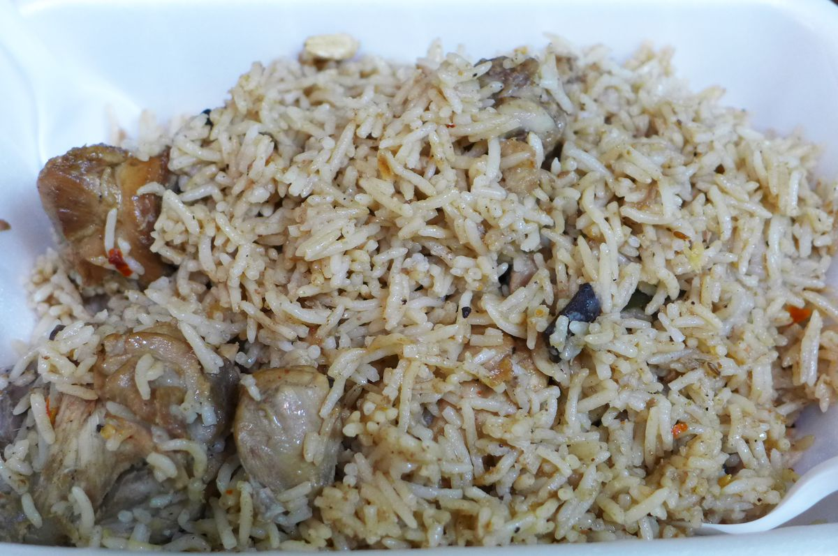 Beige rice with chunks of boneless chicken, mainly on the left side of the picture.