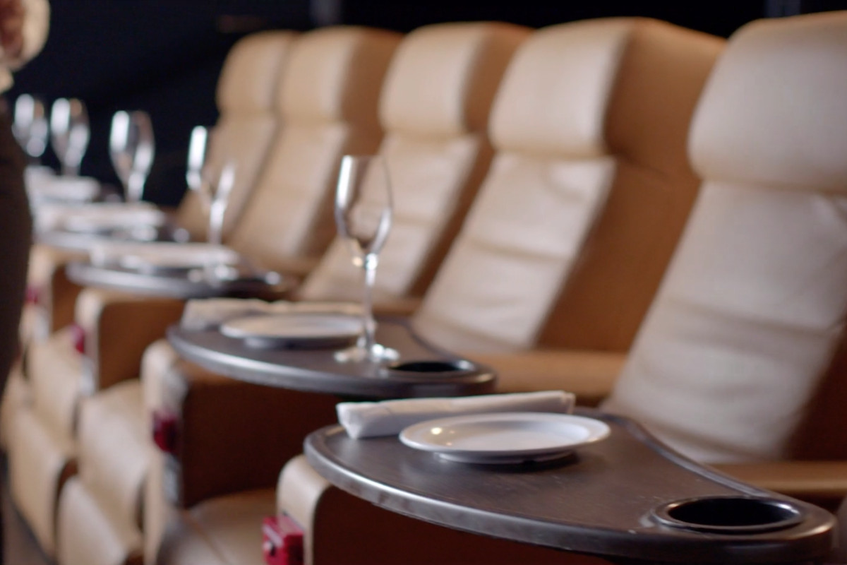 Leather seats and dinner service set ups inside of a movie theater.