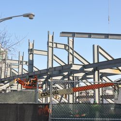Steel girder being lifted into position in the left-field bleachers -