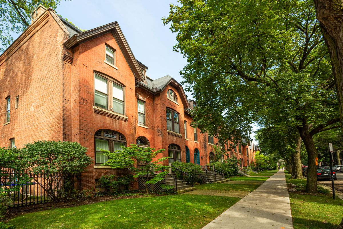 A row of brick houses in a neighborhood with a tree-lined parkway