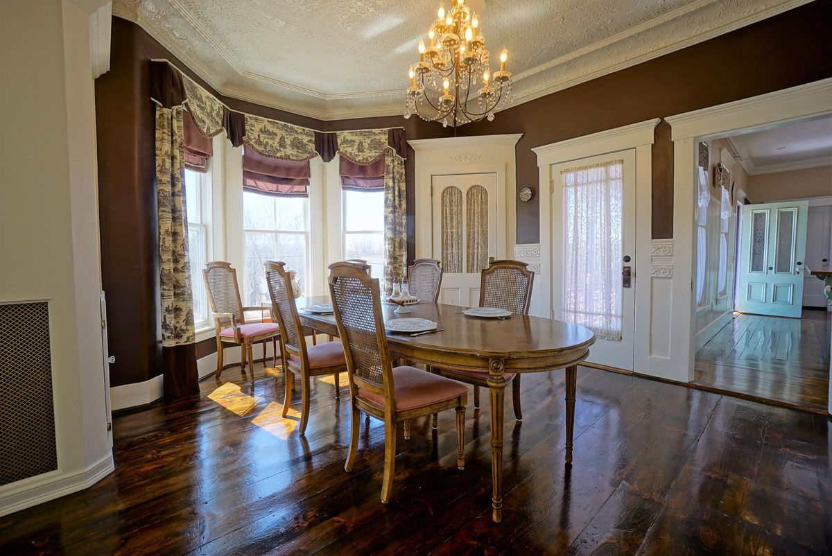 A dining room with large wood table, chandelier, and windows.