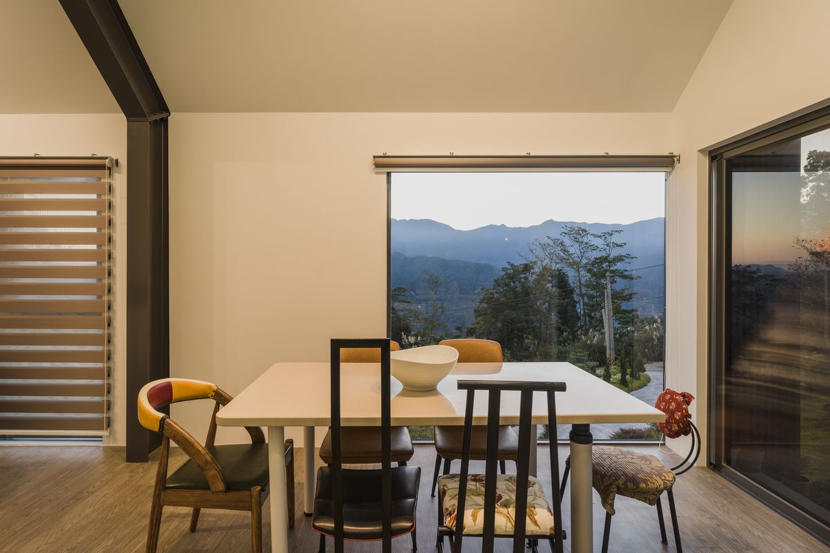 A dining table faces a large square window with mountain views.