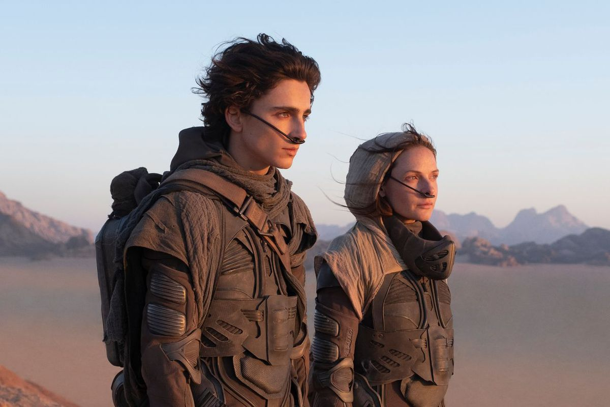 A young man and a middle-aged woman wearing futuristic suits stand in a desert.