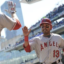 Los Angeles Angels' Maicer Izturis, right, comes in for a waiting high-five from Mark Trumbo after scoring the last of five runs in the second inning of a baseball game against the Minnesota Twins Thursday, April 12, 2012, in Minneapolis.  Trumbo had a solo home run earlier in the inning.
