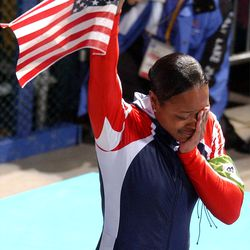 USA's Vonetta Flowers, brakeman to Jill Bakken, wipes tears from her face and waives an American flag after her and Bakken won the gold medal in the women's bobsled at the Utah Olympic Park on Tuesday, Feb. 19, 2002.