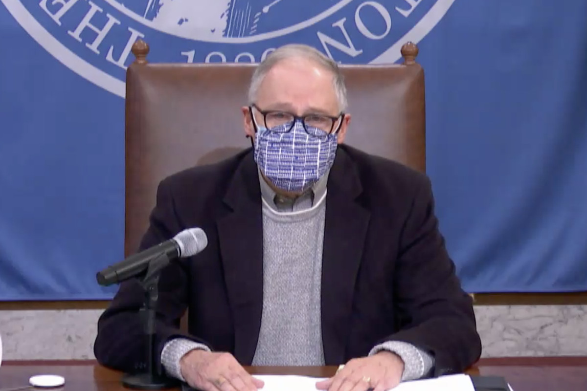 Gov. Jay Inslee of Washington sits in a leather chair at a press conference, wearing glasses and a mask