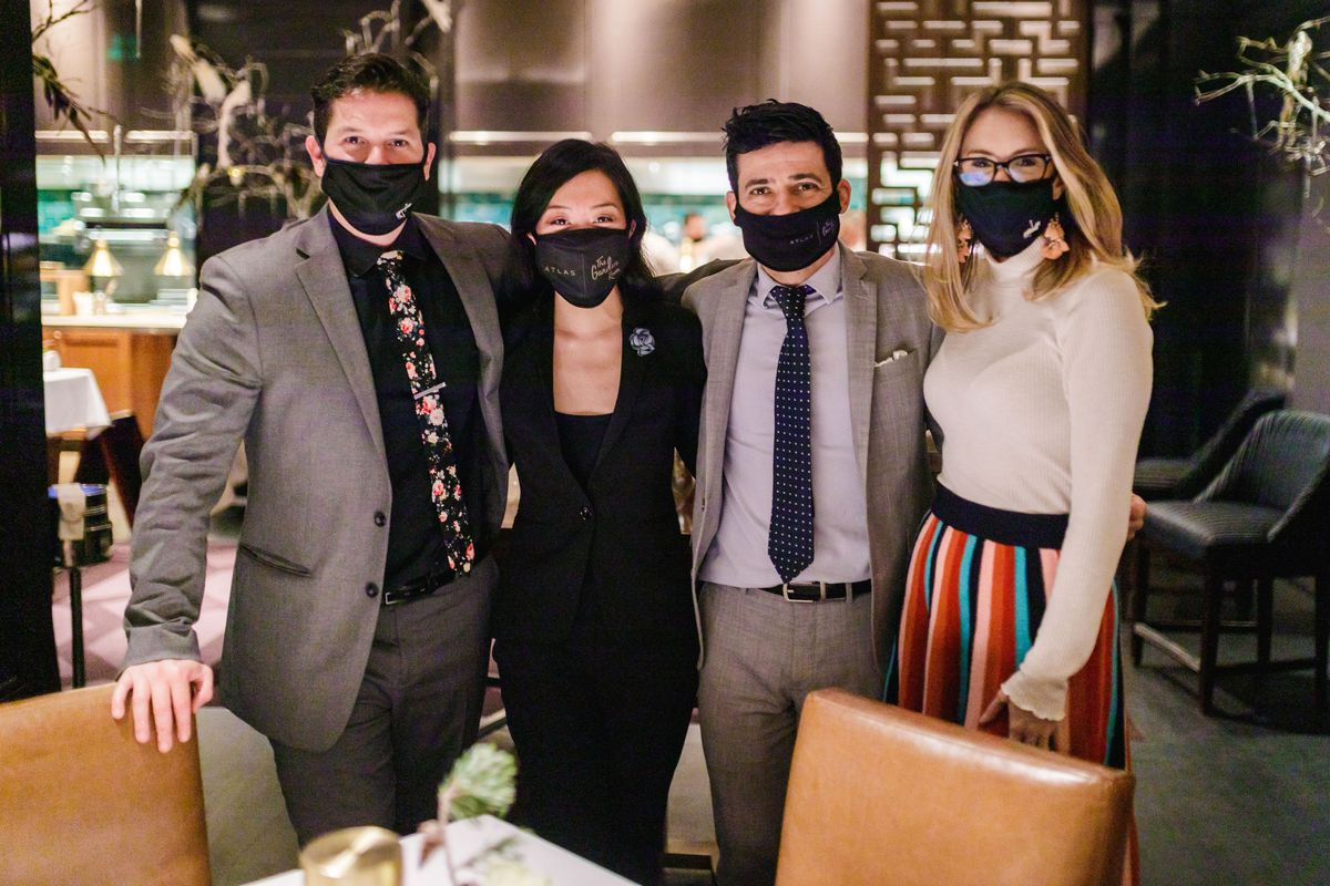 Four sharply dressed female and male staff members in custom logo black masks in the dimly lit dining room at Atlas in Atlanta