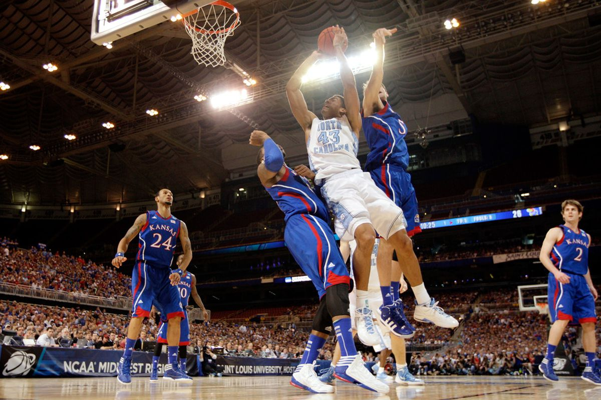 James Michael McAdoo drives for a shot attempt in the first half against Thomas Robinson #0 and Jeff Withey #5 of the Kansas Jayhawks.