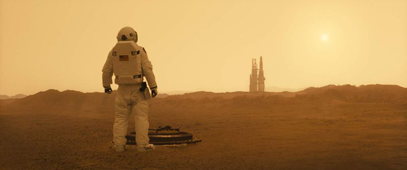 "A man in a spacesuit looks across a barren plain toward a rocket on a launch pad in the movie ""Ad Astra."""