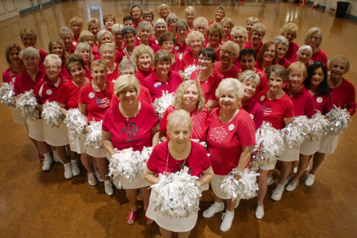 A large group of senior citizens in cheerleaders' costumes stand in a triangle formation.