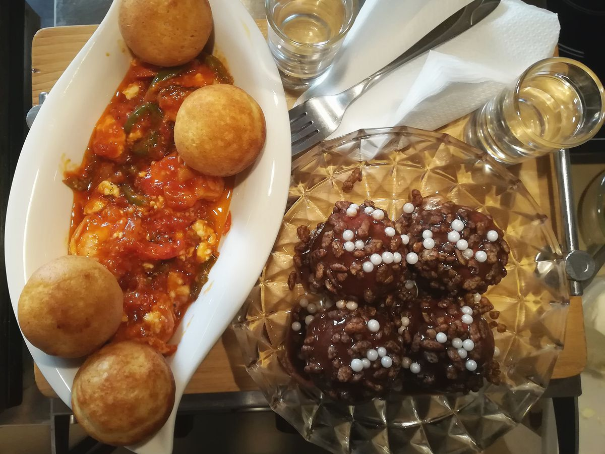 From above, a ceramic dish of puff balls in savory tomato sauce, and a glass bowl of chocolate puffs topped with pearl sugar, along with two small drinks on a tray