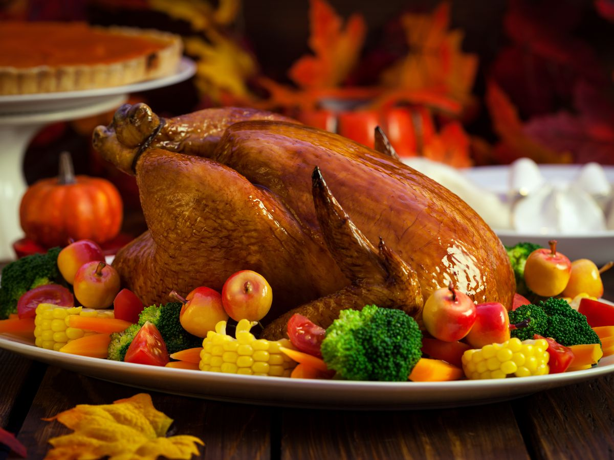 A stock photograph of roasted Thanksgiving turkey sitting on platter garnished by vegetables. A pumpkin pie is visible in the background.