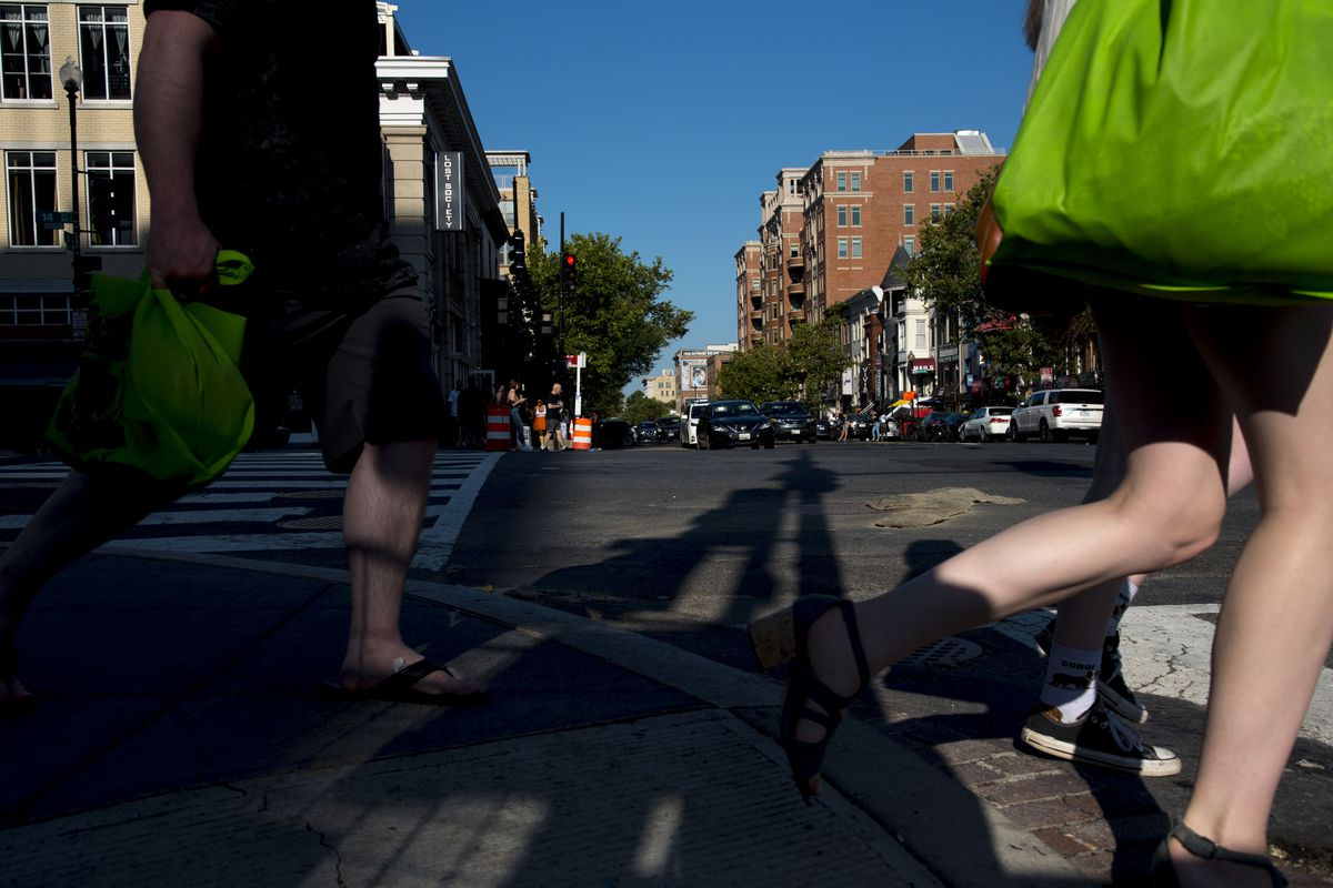 People's legs are shown as they cross a four-way intersection in a city.