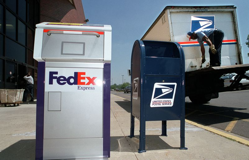 A FedEx box and a USPS box on a sidewalk beside a postal delivery truck.