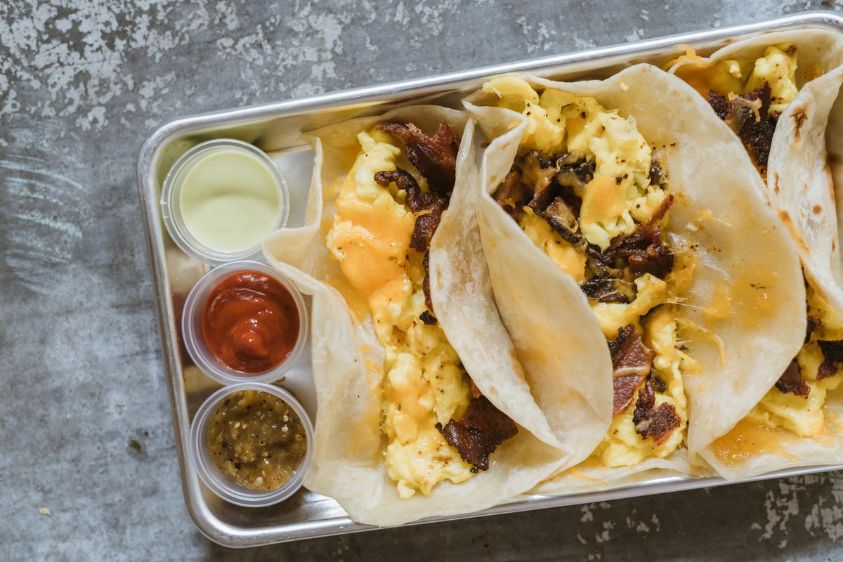 a tray holds three salsas and 3 breakfast tacos filled with egg and meat and cheese