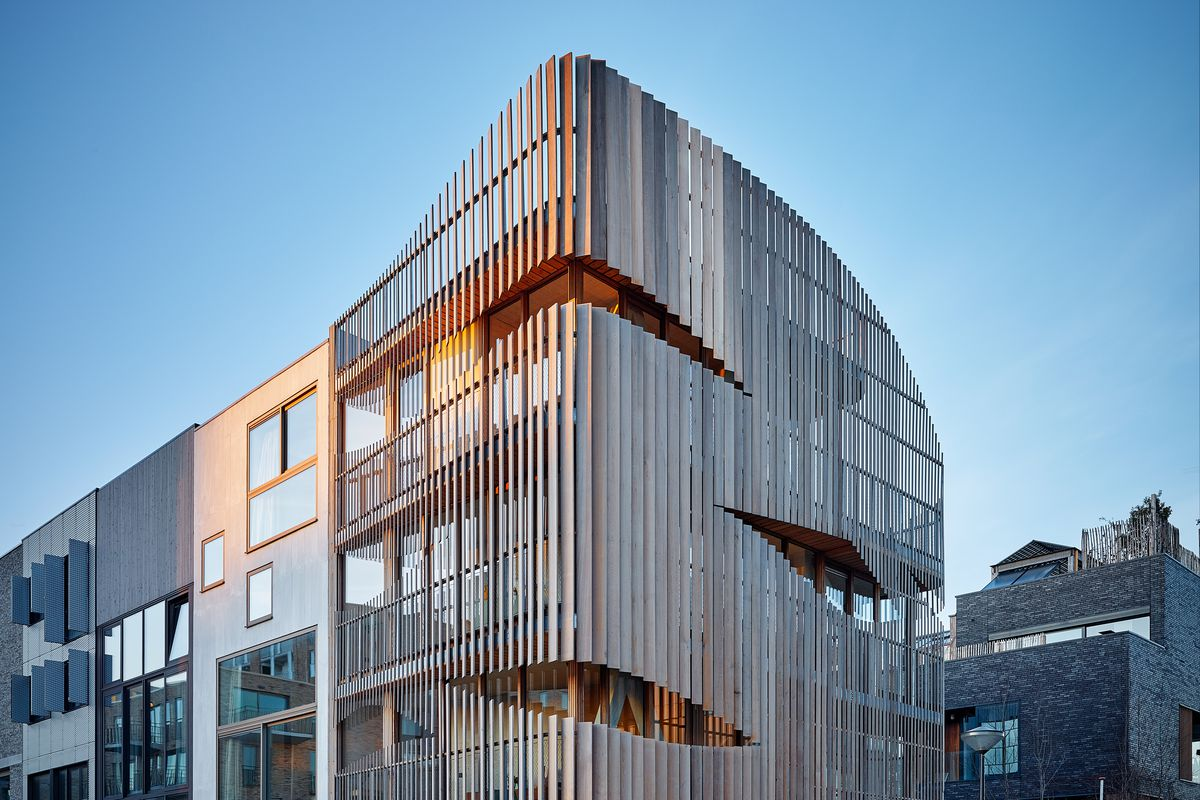A building with curved edges wrapped in wooden louvers.