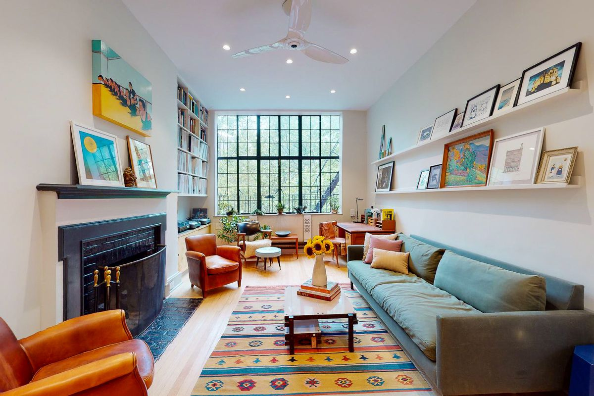 A living room view of a bright and airy one-bedroom apartment for sale in the Tudor City neighborhood of New York City. The room has a fireplace, gray couch, and casement windows on the far side.