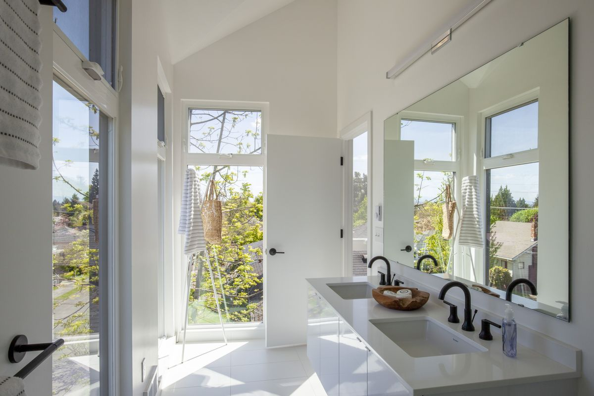 A light filled bathroom with a wall of glass and white countertops.