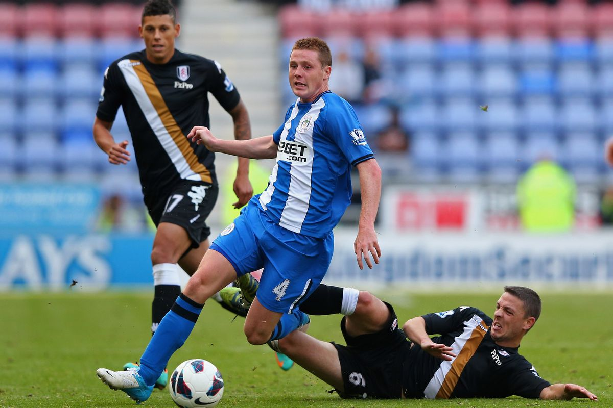 James McCarthy of Wigan Athletic is fouled by Chris Baird of Fulham during the Barclays Premier League match between Wigan Athletic and Fulham at DW Stadium.