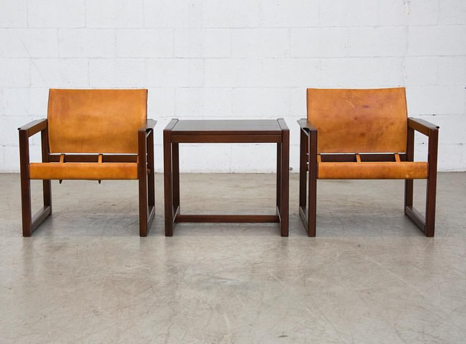 Two orange arm chairs next to a brown table.