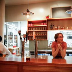 Team members relax at Homeroom's bar, with four beers on tap.