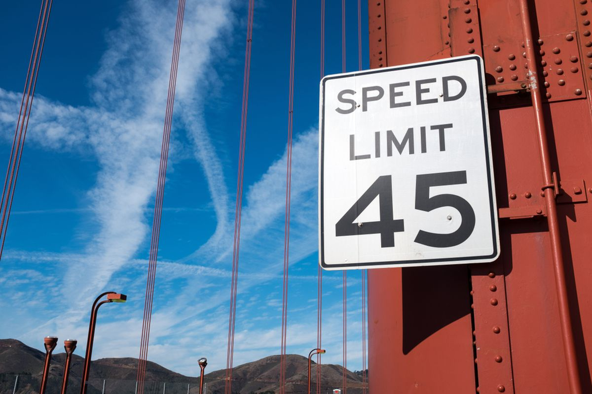 A sign posting a 45 mile per hour speed limit, attached to an orange-painted girder on a suspension bridge (the Golden Gate Bridge).