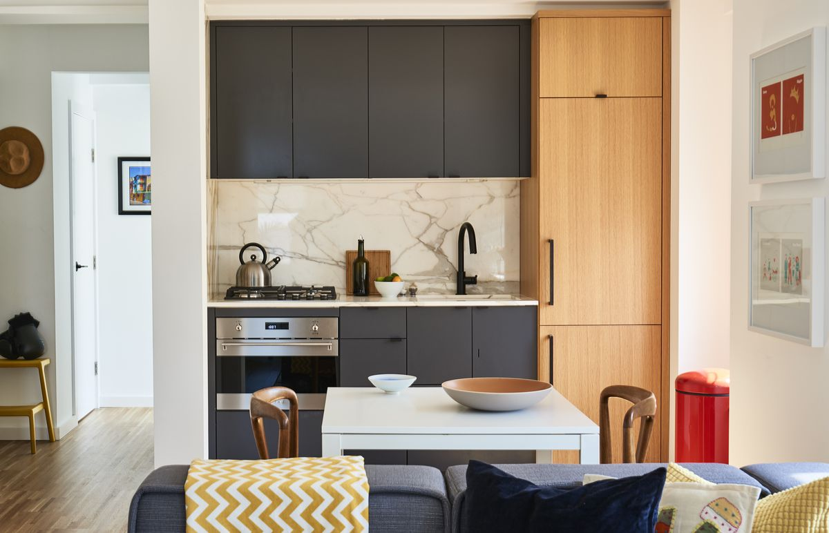A Small Kitchen Has Gray Cabinets With Column Of Natural Wood For Contrast