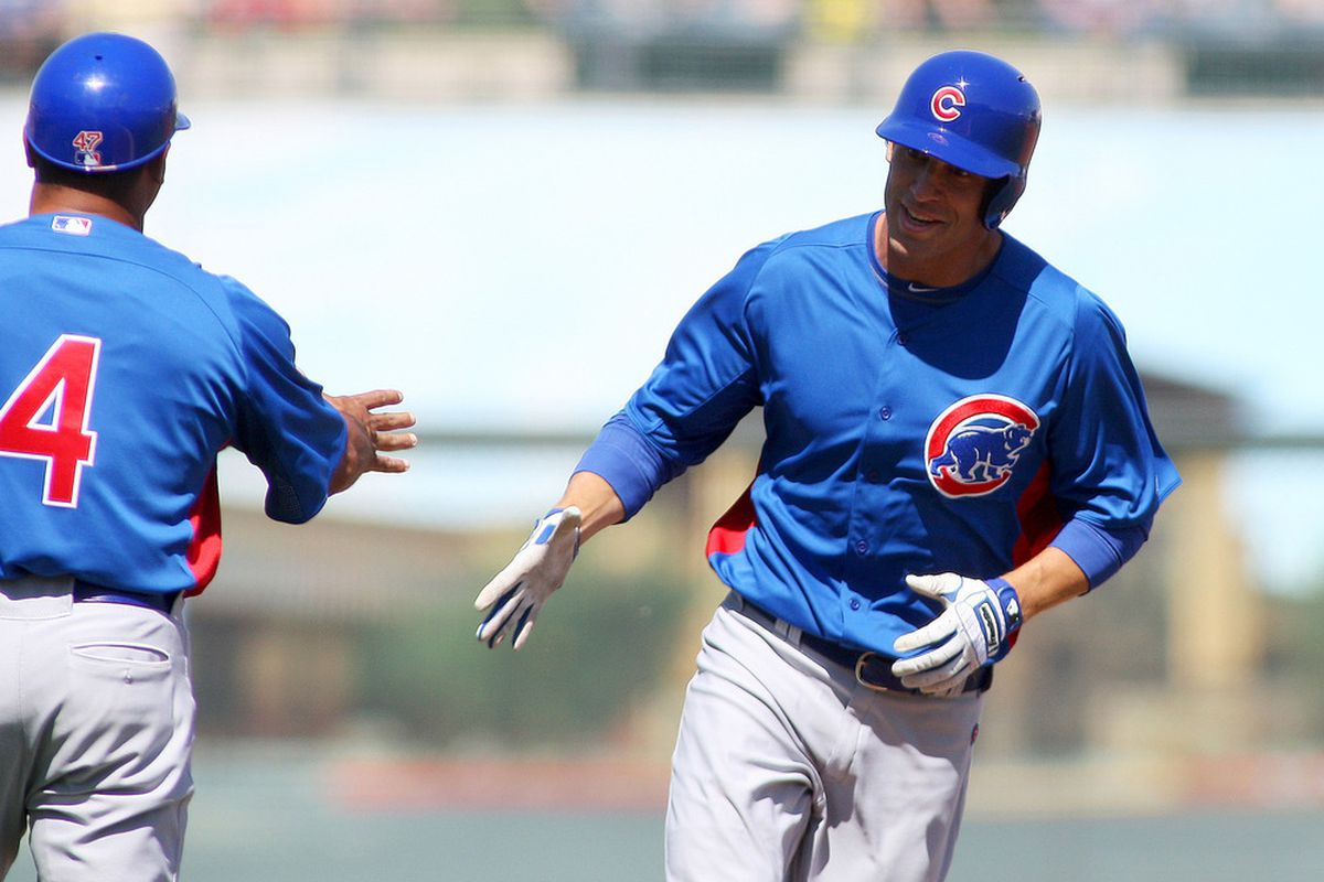 Surprise, AZ, USA; Chicago Cubs center fielder Joe Mather is congratulated by third base coach Pat Listach after hitting a two run home run during the second inning at Surprise Stadium. Credit: Jake Roth-US PRESSWIRE