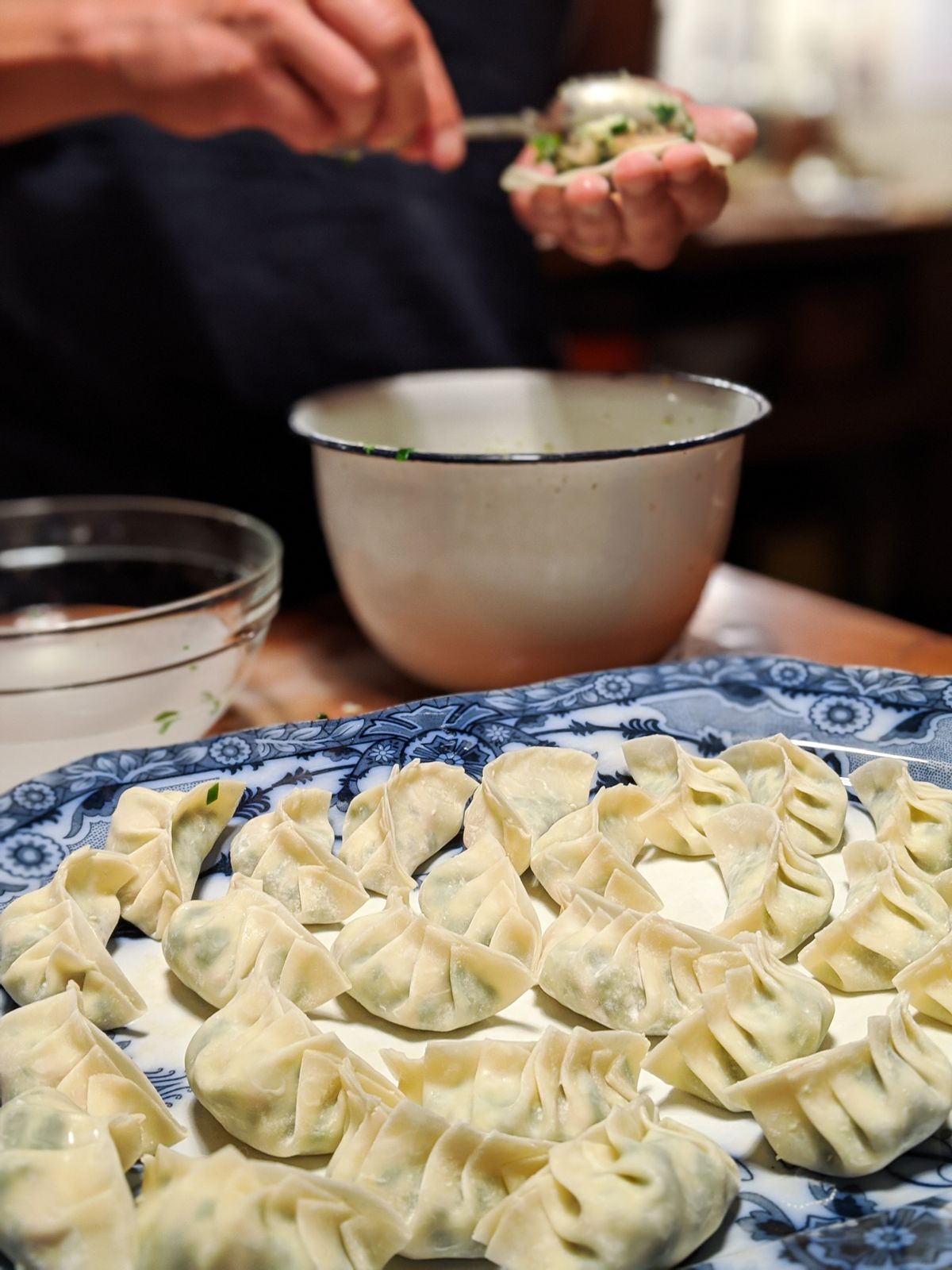 A plate of finished, uncooked dumplings with pleated edges