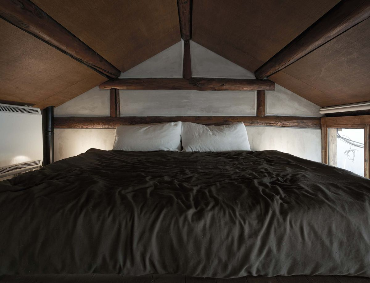 Bed tucked into lofted nook.