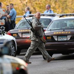 An officer walks through the area as police investigate a shooting at Accent Signage Systems on the north side of Minneapolis Thursday, Sept. 27, 2012. Police say left at least two people were killed and four others wounded.
