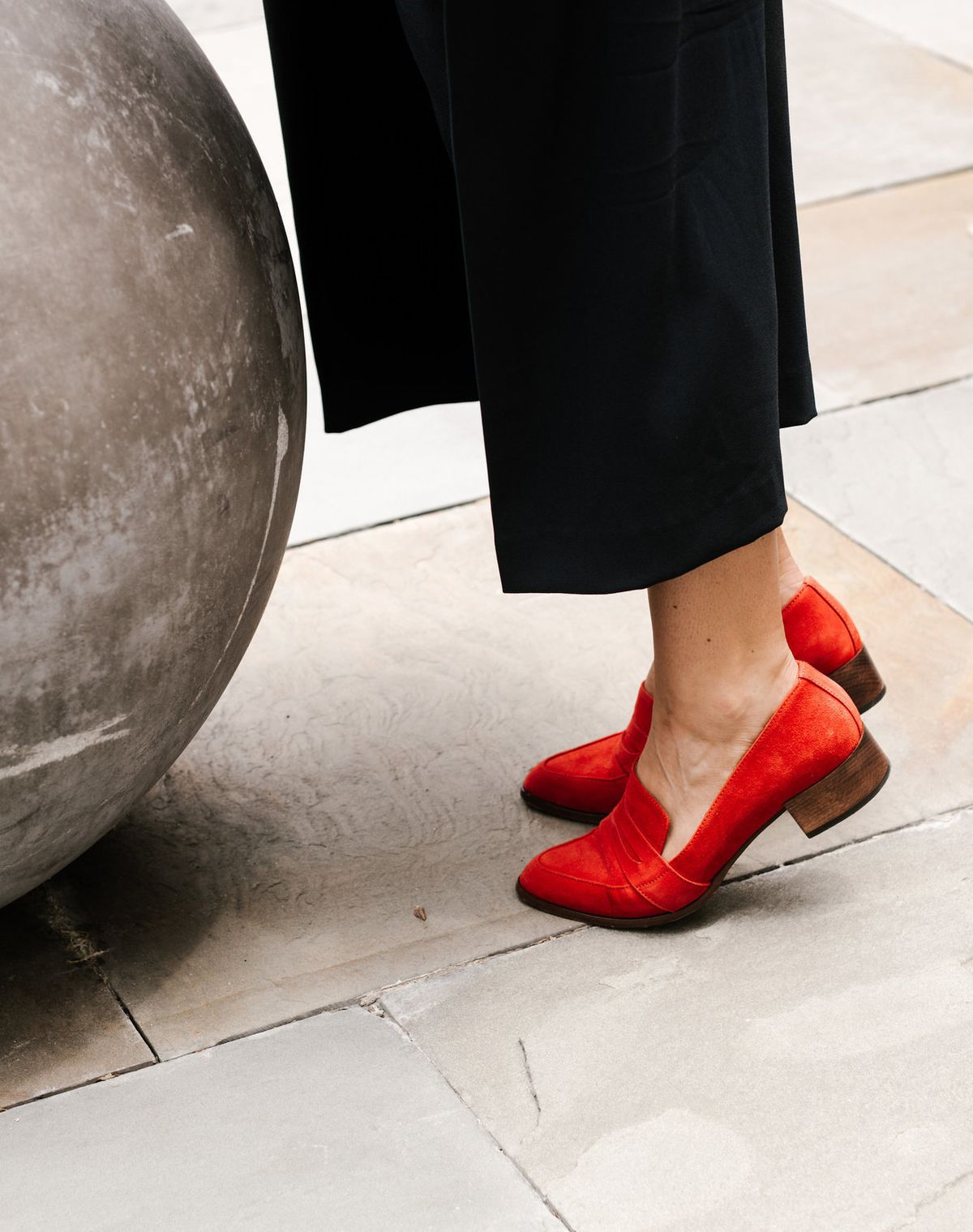 A woman wearing red loafers and black pants, shown from the waist down