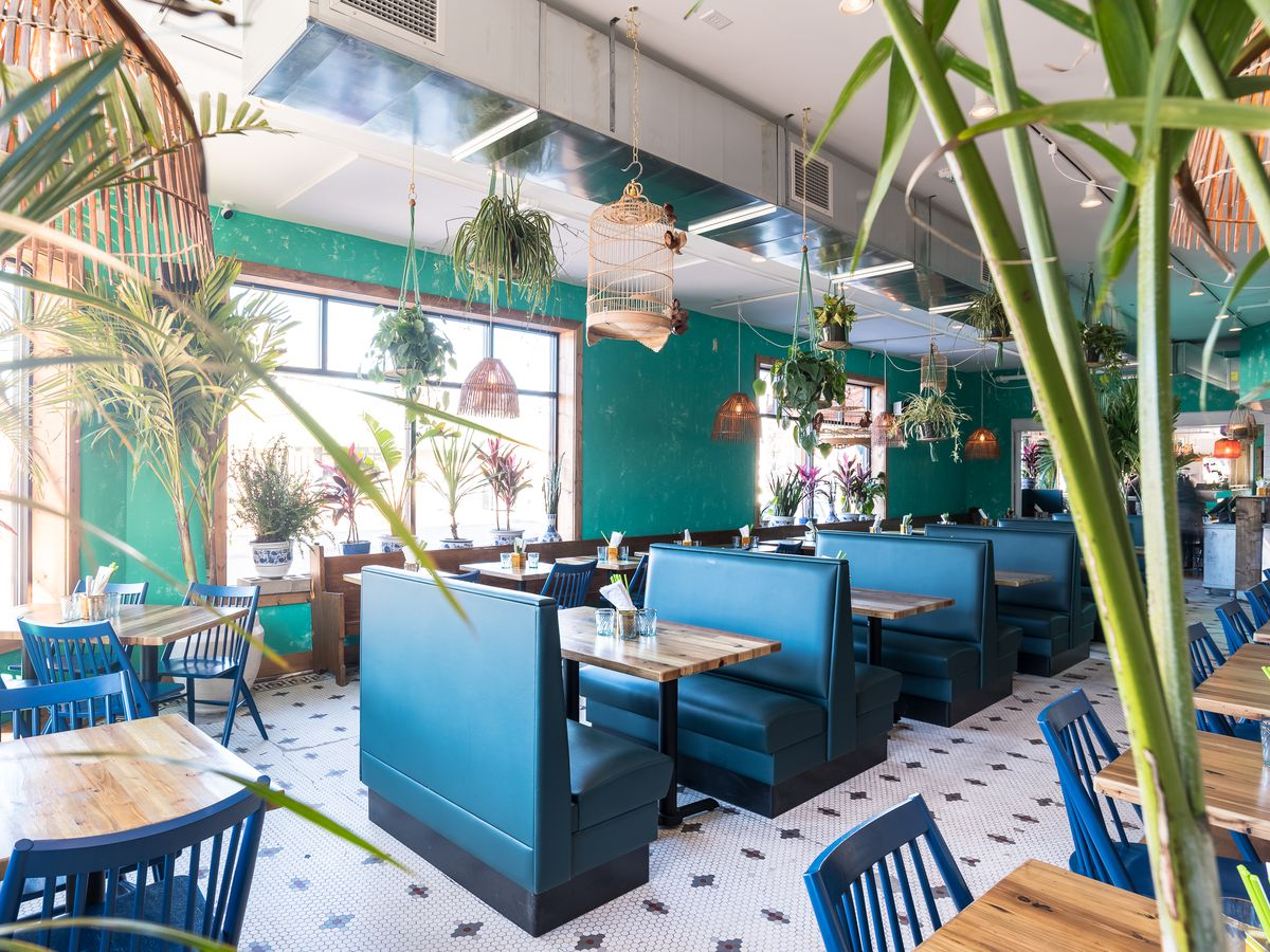 The brightly colored blue interior of Hai Hai, decorated with palm tree plants